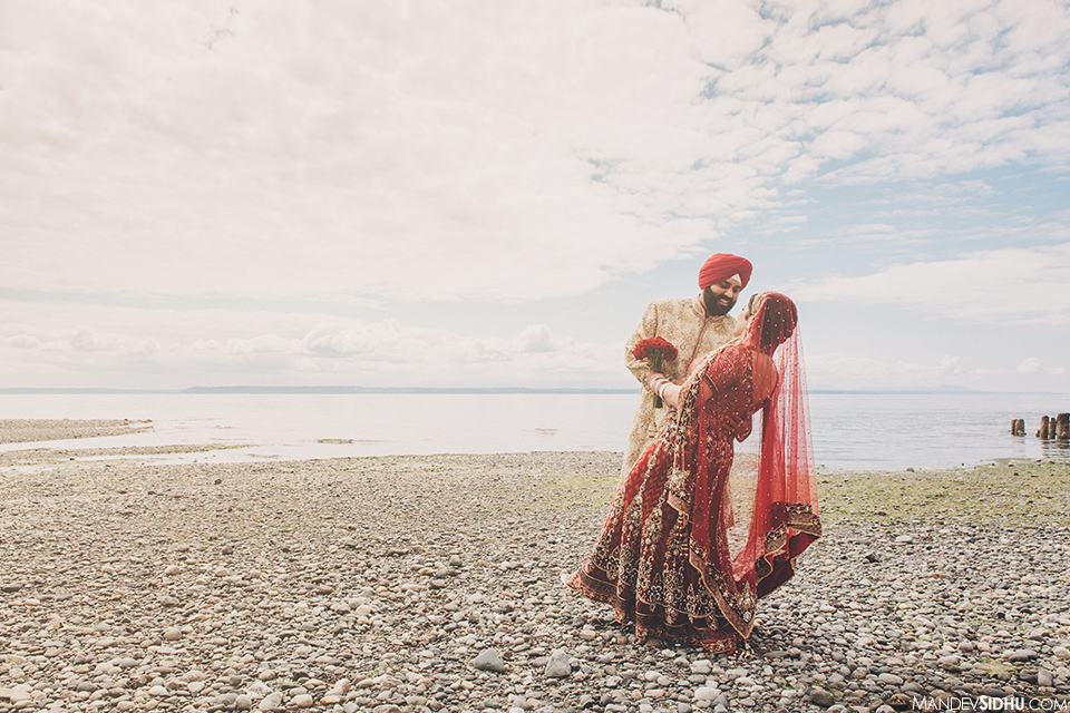 Photograph of Indian bride and groom standing on the beach on their wedding day