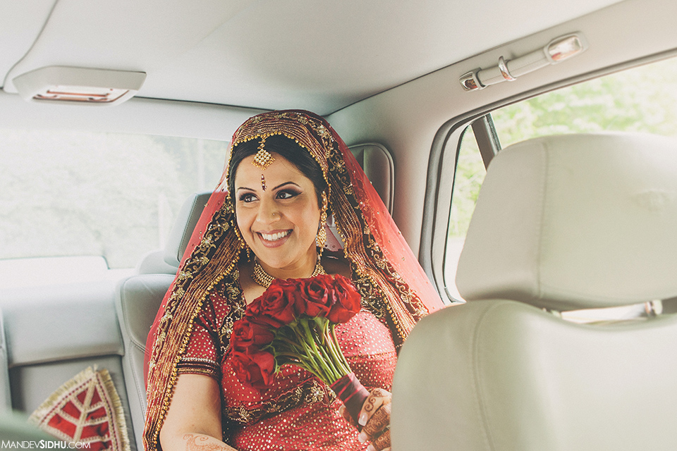 Indian bride wearing red Lehenga sitting in car