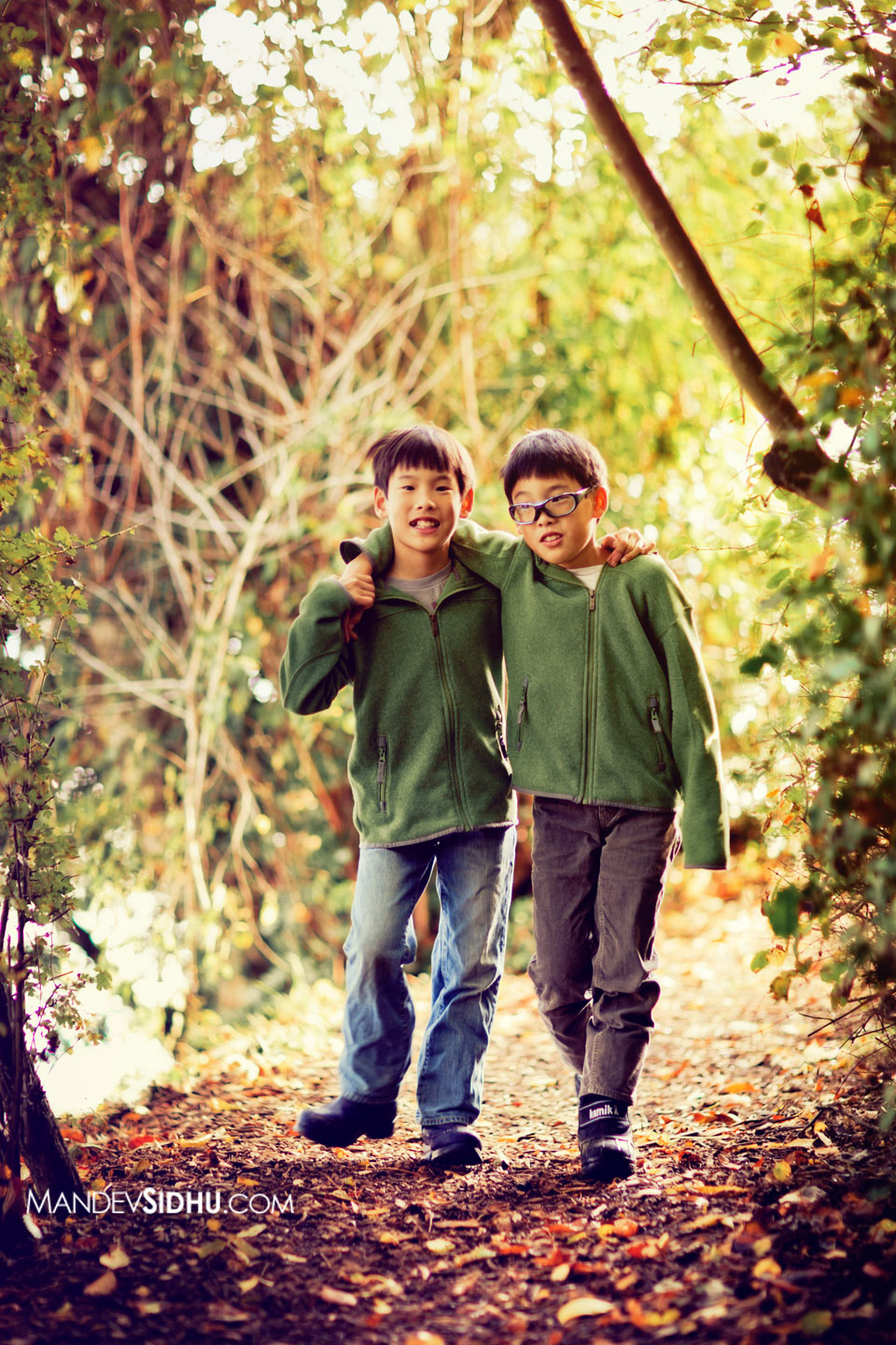 Twin boys walking along a trail in the park