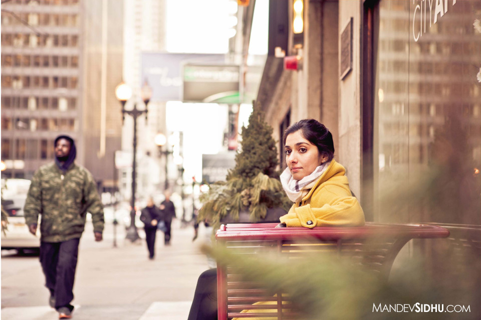 Sitting on a bench in Downtown Chicago wearing a yellow coat