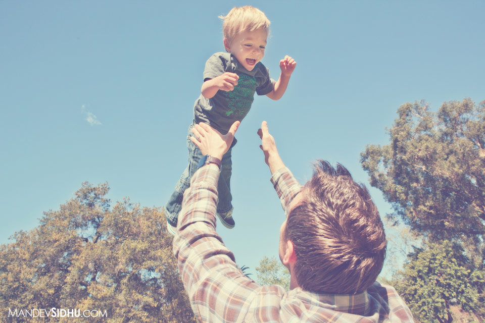 Father throwing son into the air while they play