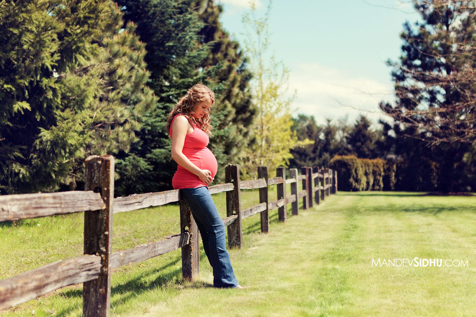 country style maternity mother holding belly wooden fence