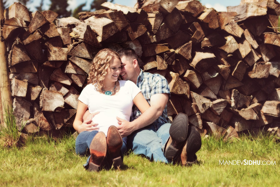 country-style maternity photos sitting next to woodpile