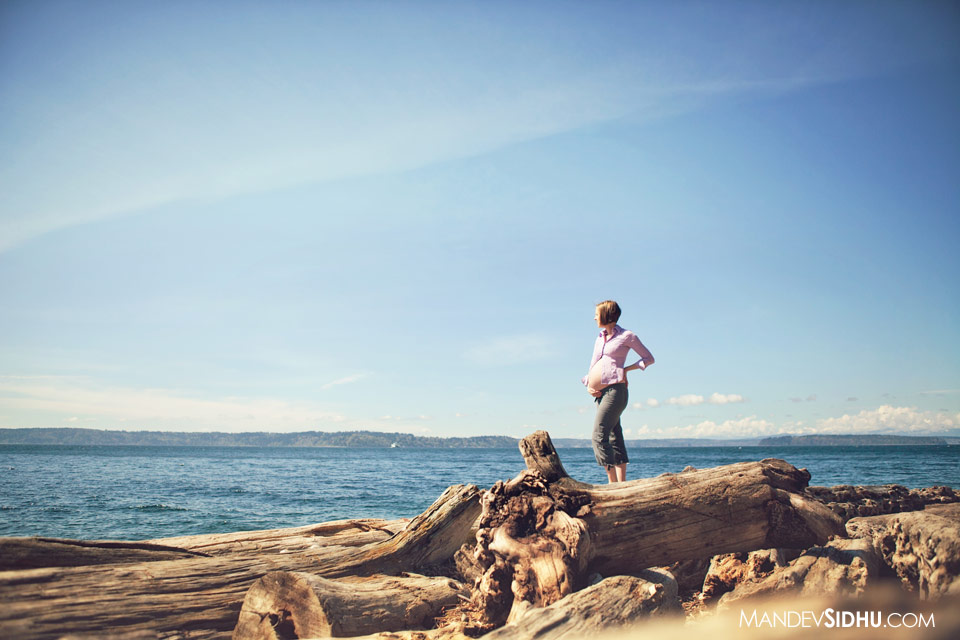 seattle maternity photography mother standing on log at beach