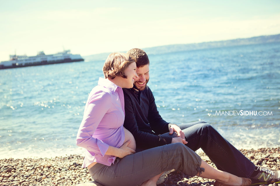 seattle maternity photography couple sitting on a log at the beach pregnant belly