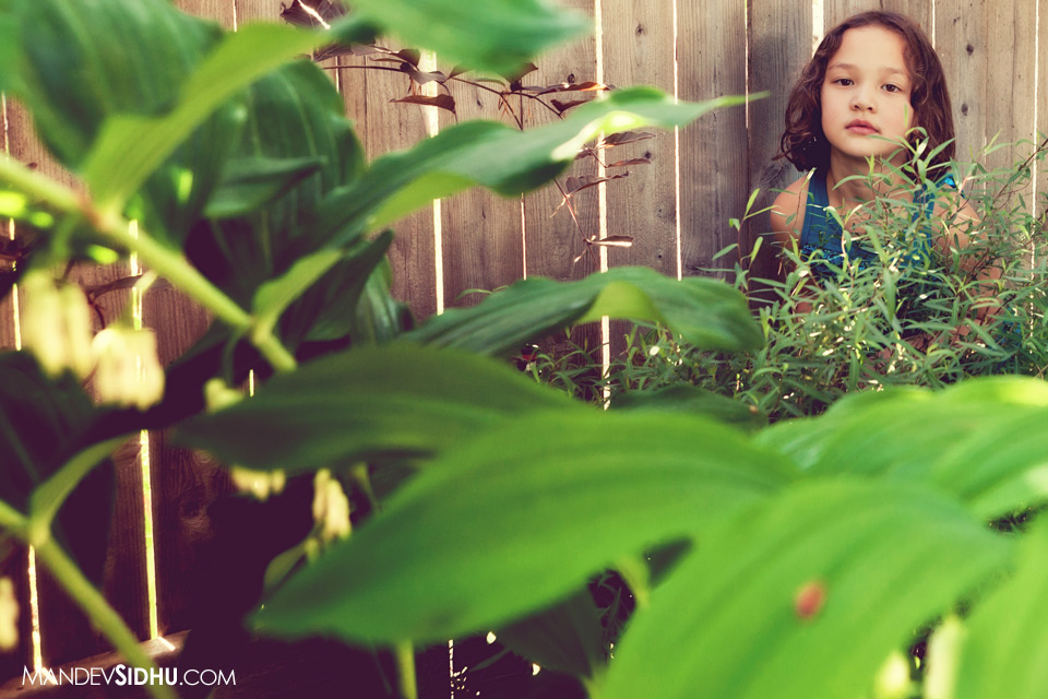 daughter playing in flowers in backyard