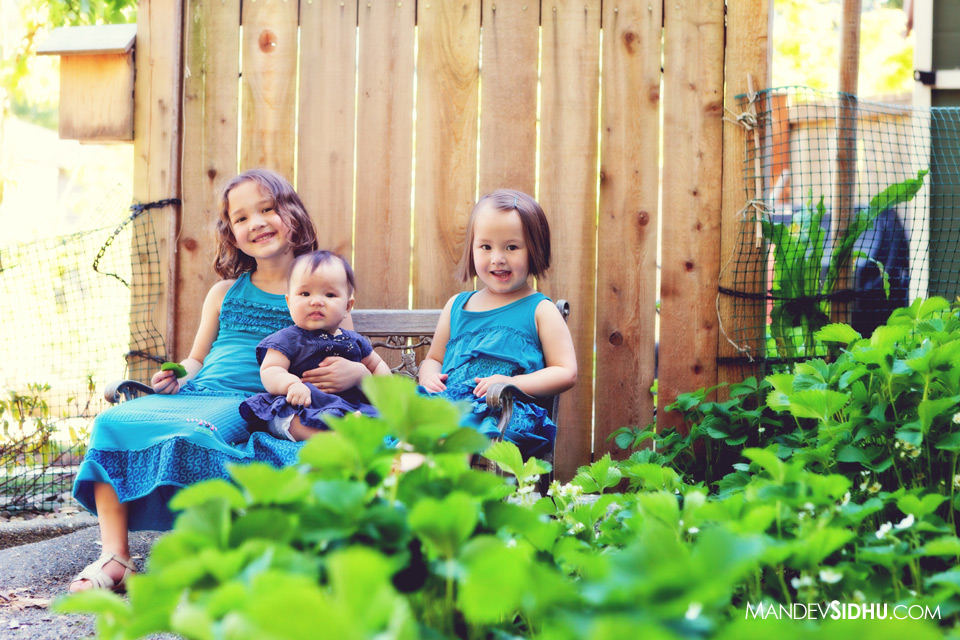 photo of three cute sisters sitting on bench