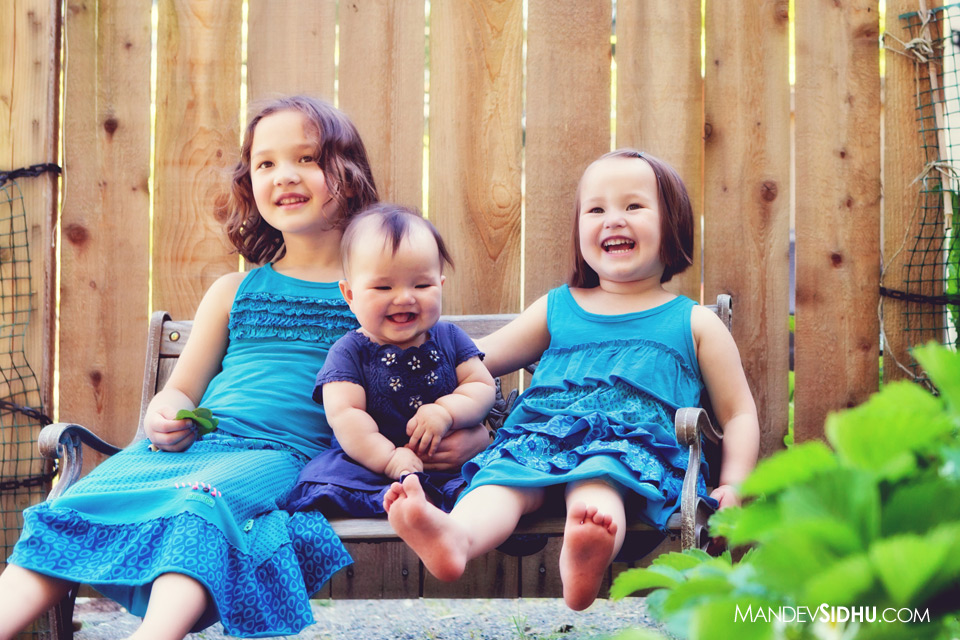 photograph of three adorable happy sisters on bench