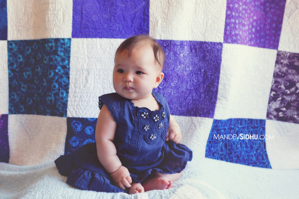 newborn daughter sitting in front of a beautiful hand-made checkered quilt
