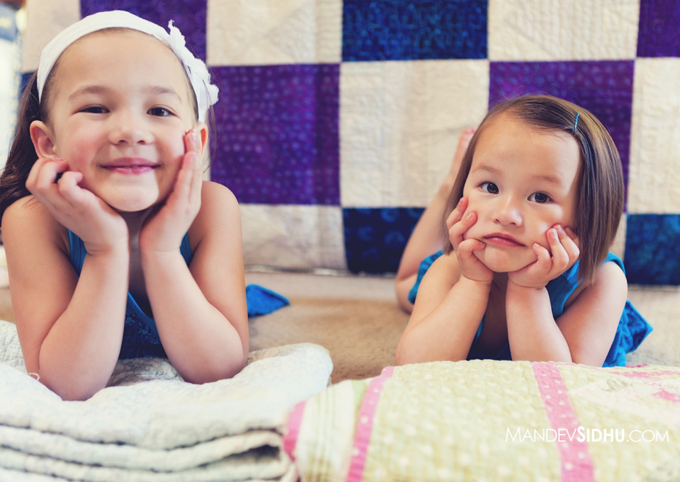 portrait of two adorable sisters laying in front of beautiful hand made quilt