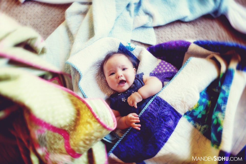 cute happy newborn baby girl laying in hand-made quilts