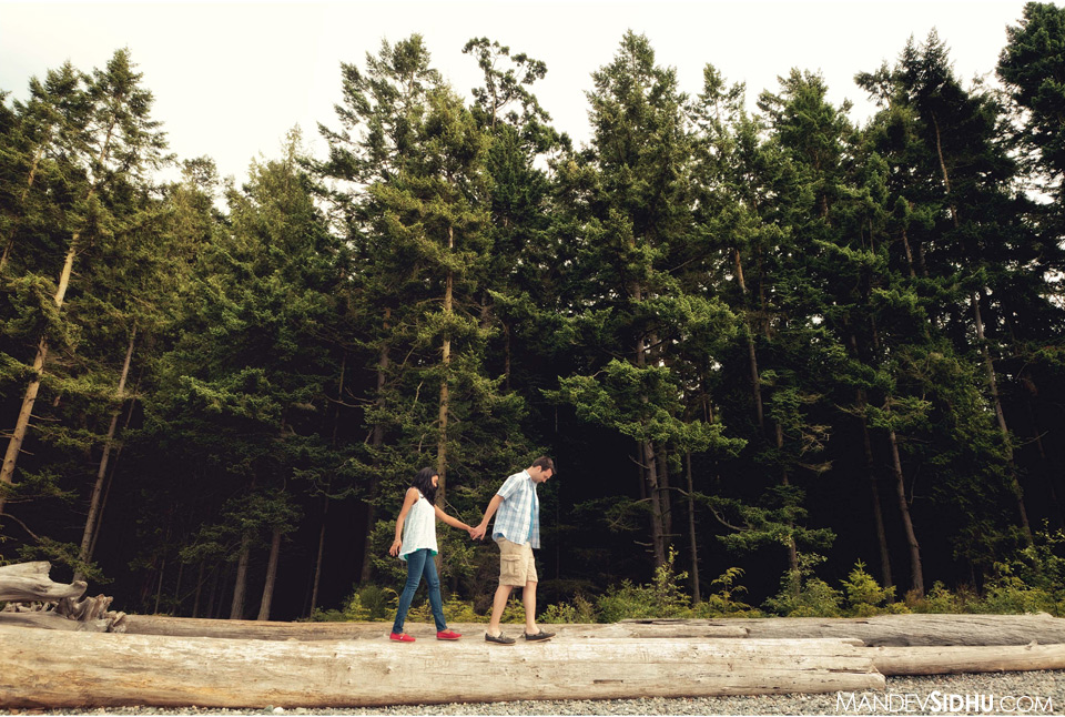 walking on logs at beach engagement photo