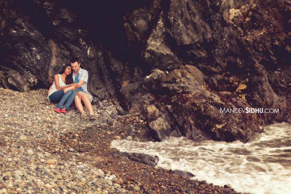 engaged couple sits on beach in a rocky cove