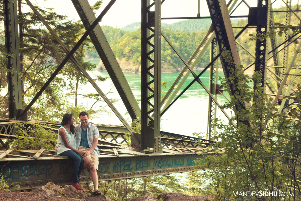 couple sitting on Deception Pass bridge Whidbey Island