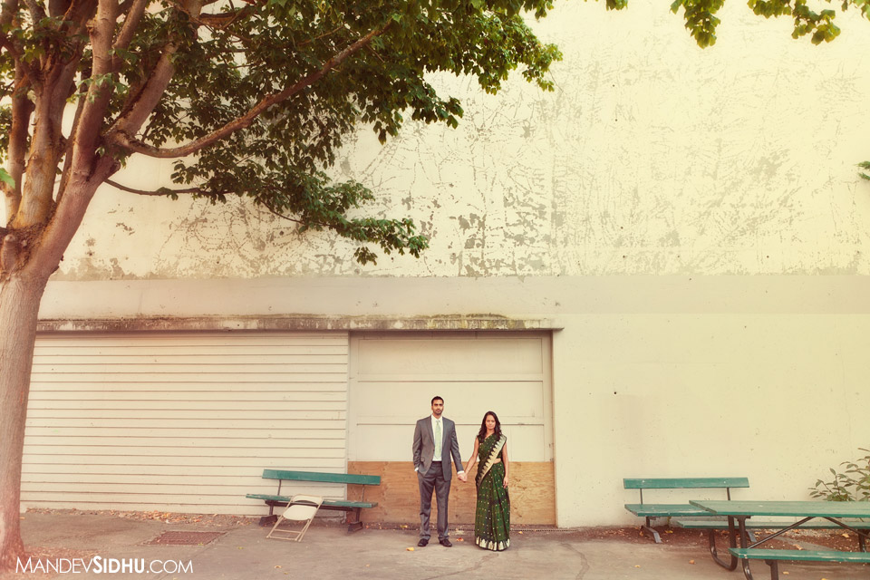 couple standing next to old building