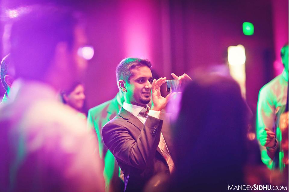Groom taking photo on dance floor