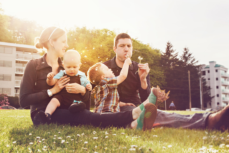 family sitting in the grass blowing dandelions in the sun