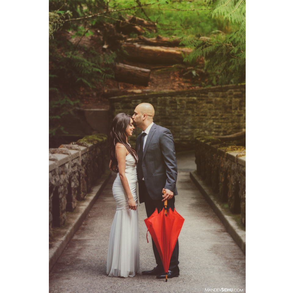loving engagement photo with red umbrella on old bridge