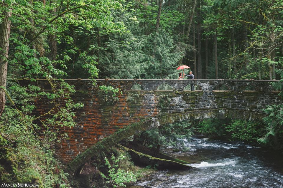 engagement photo with red umbrella on old stone bridge