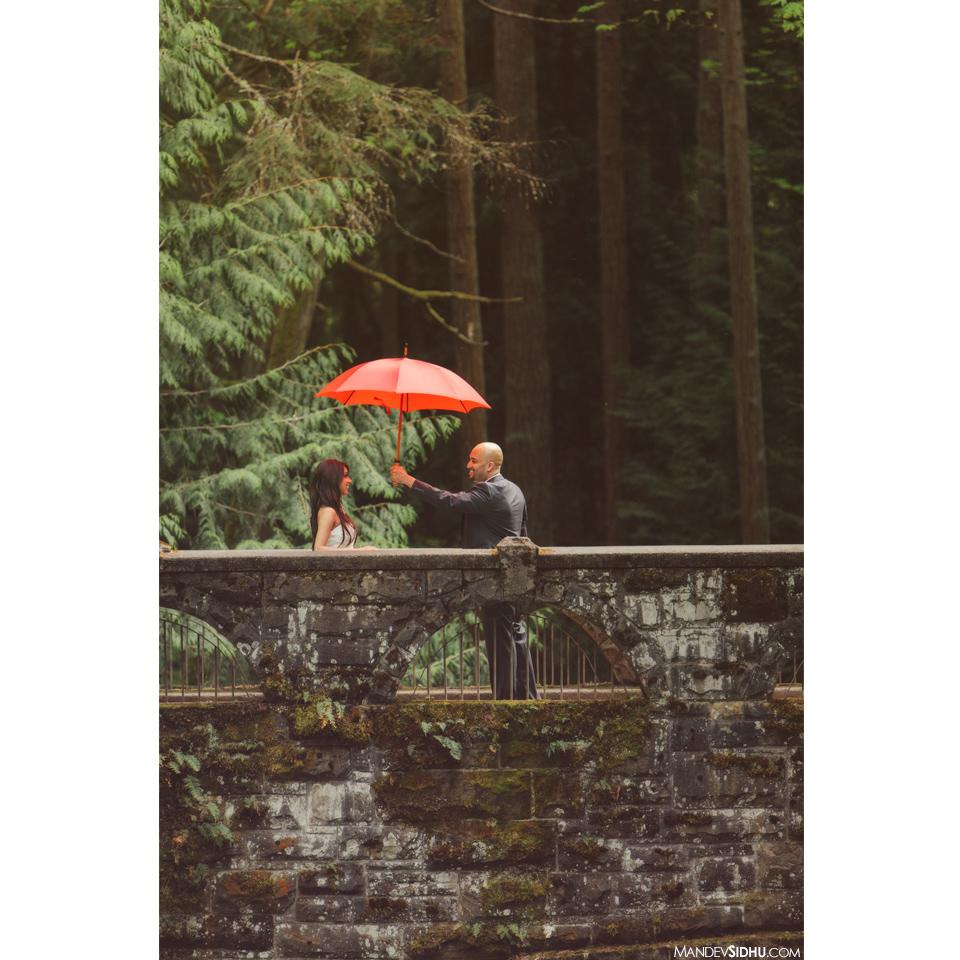couple holding red umbrella engagement photo on old stone bridge