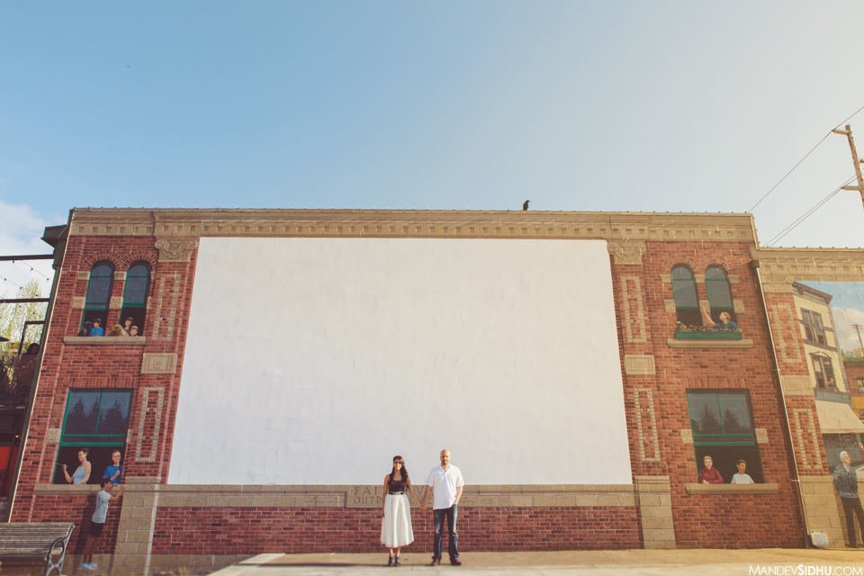 cute couple holding hands in front of brick wall