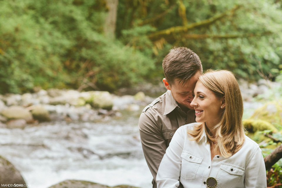 Happy loving couple standing next to river engagement photo in Seattle