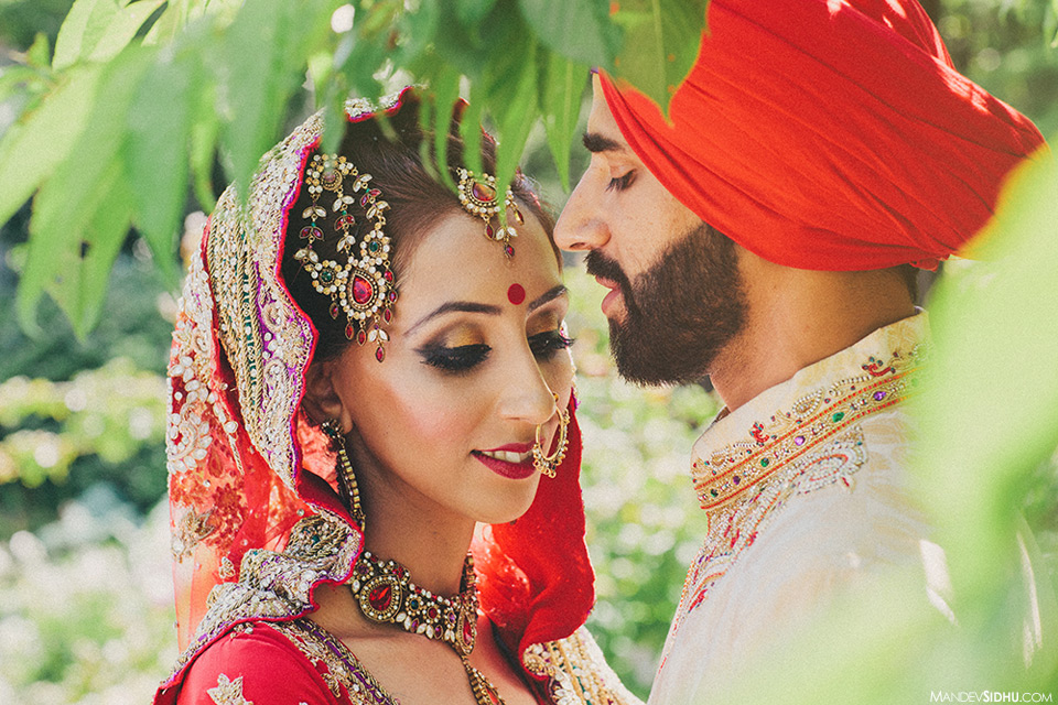 Portrait of Sikh bride and groom wearing red, and standing in the trees