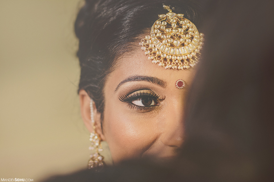 Sikh Bride getting her makeup done before ceremony