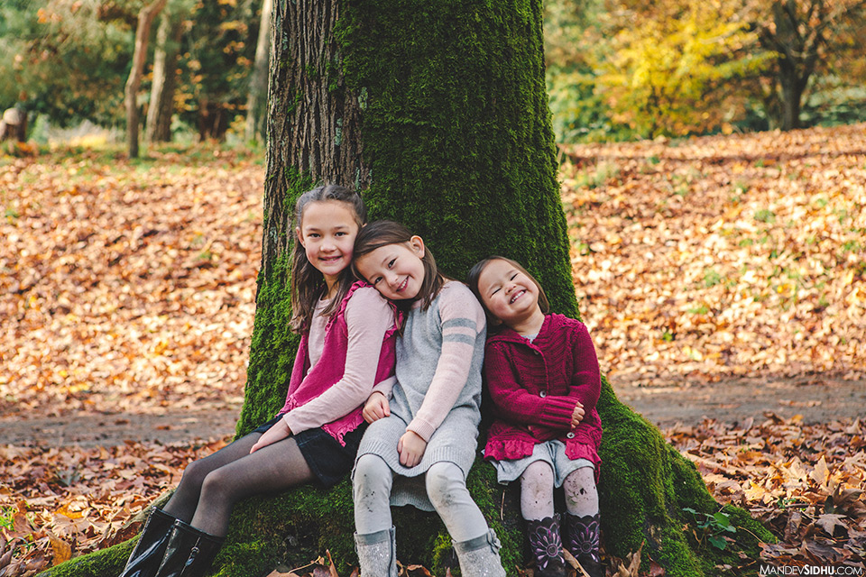 3 sisters family photo sitting against a tree in the park