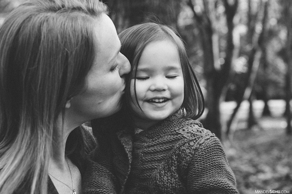 beautiful emotion as mother kisses daughter on cheek for family photo in a Seattle park