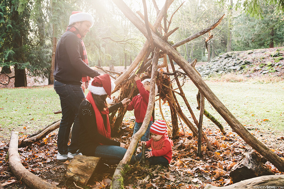 Family in Wooden tepee built with long wooden sticks