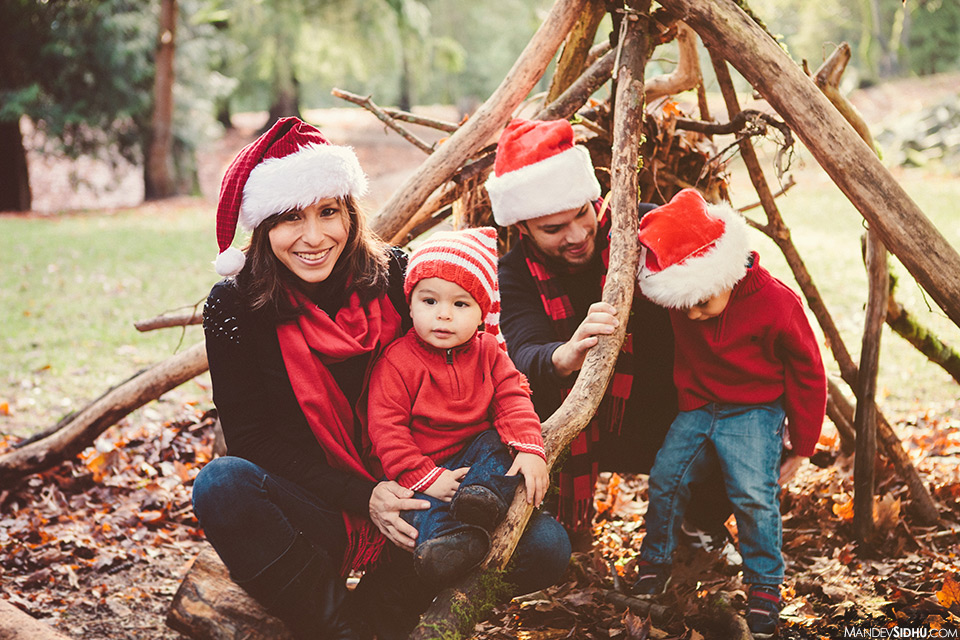 christmas family photo in wooden teepee built with long wood sticks