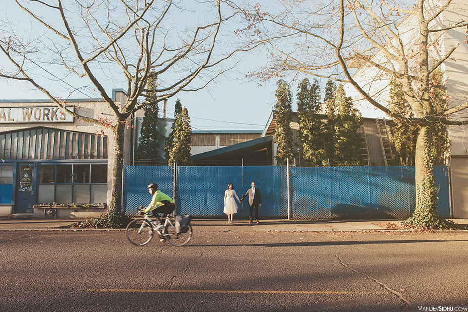 Couple stands in front of blue fence in downtown Ballard for engagement pics