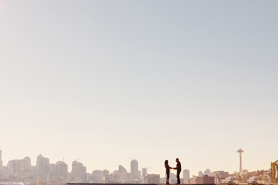 Couple stands in front of Seattle skyline for engagement photos
