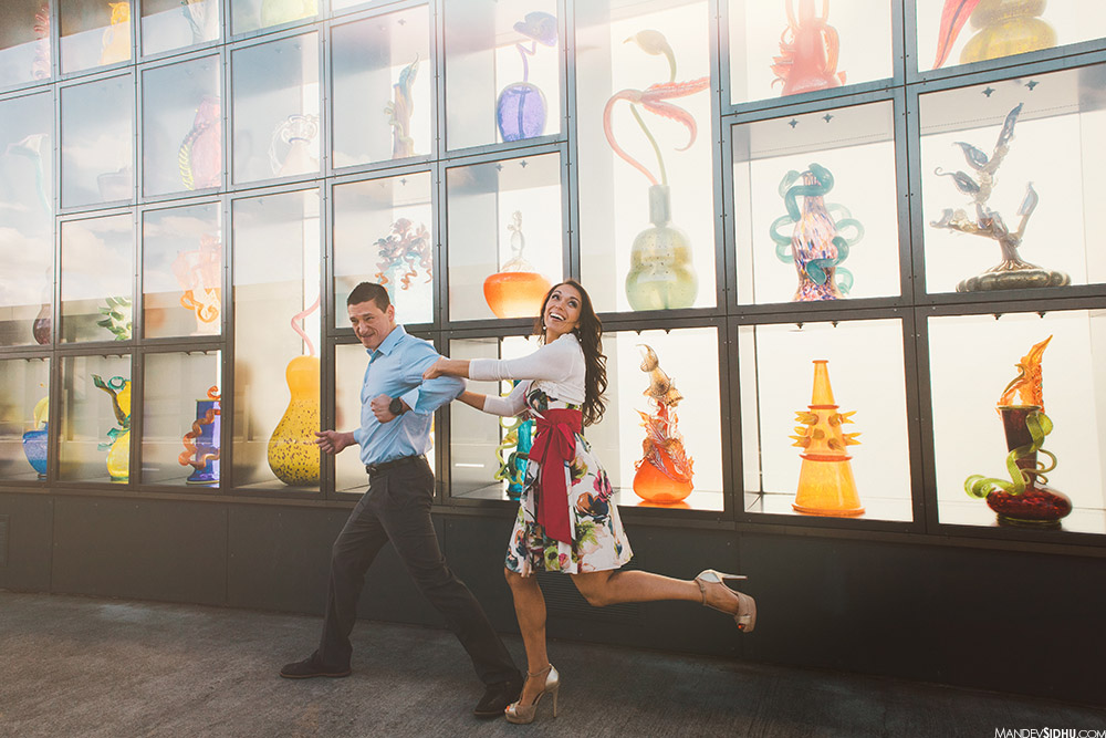 fun engagement photos in Tacoma with Chihuly glass art in the background