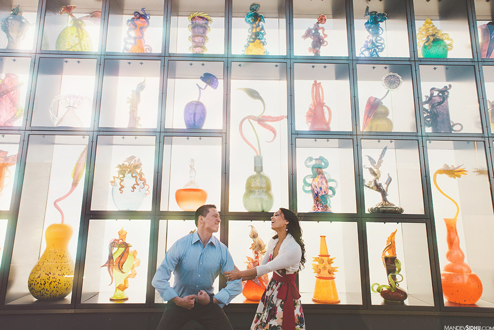 funny couple standing in front of chihuly art for engagement session
