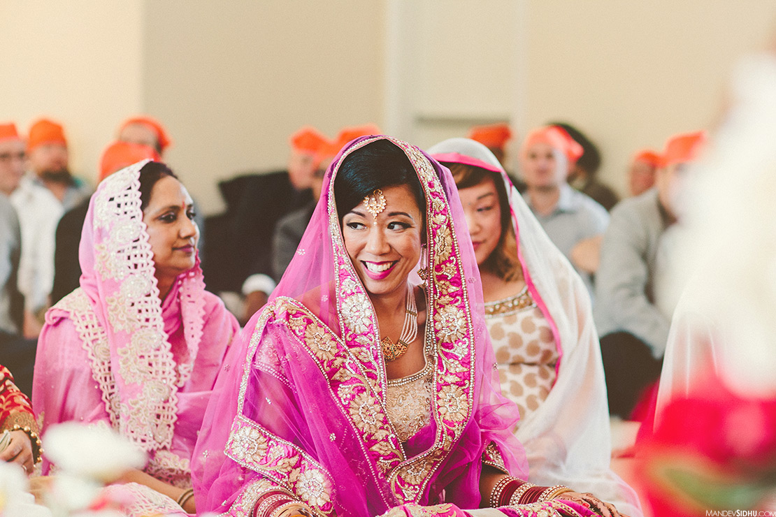 happy indian bride smiling during anand karaj ceremony