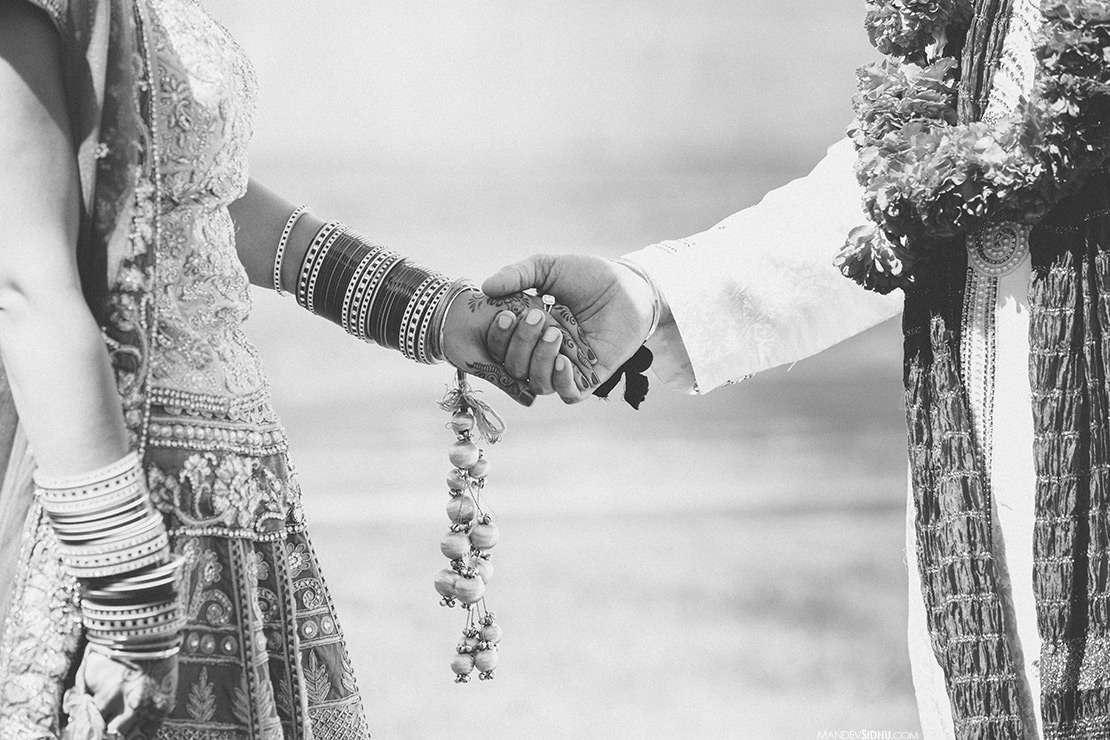 Sikh bride and groom holding hands