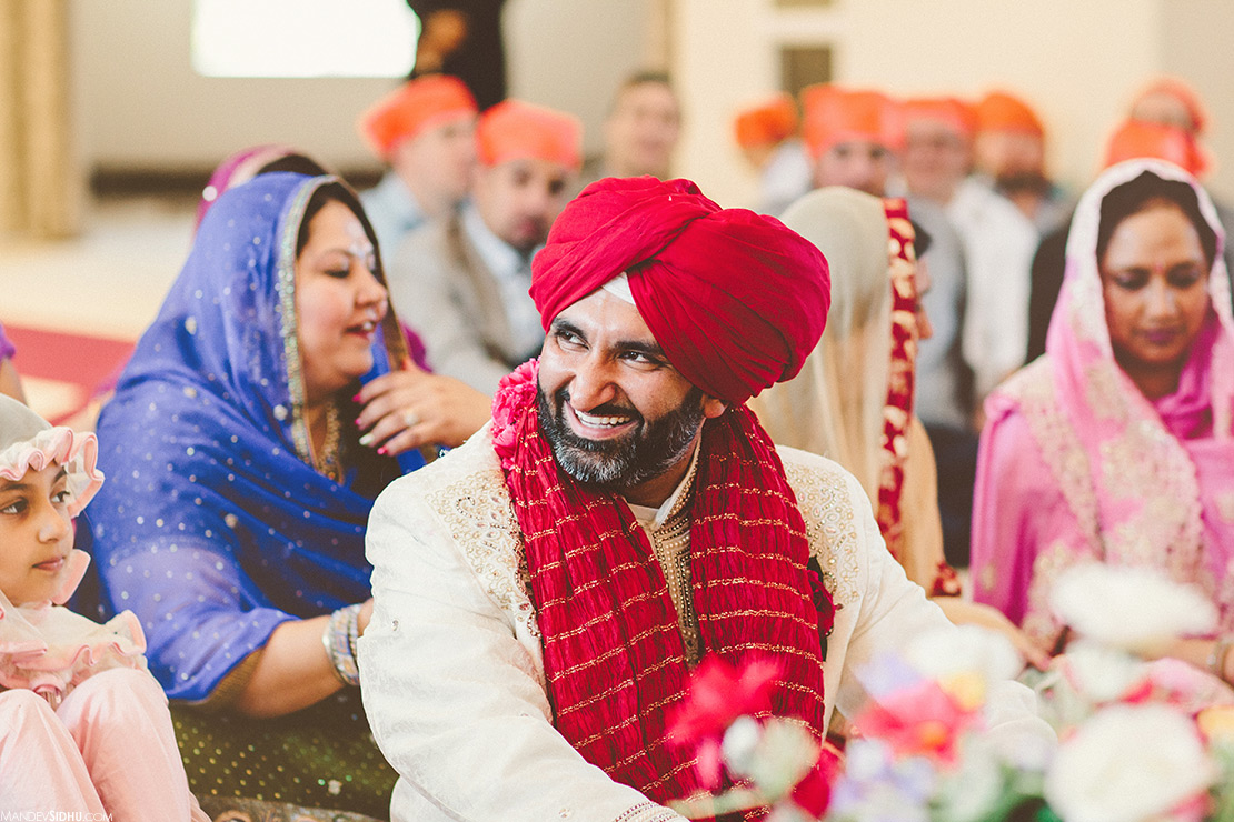 happy Sikh groom smiling during anand karaj ceremony during Indian wedding in Seattle