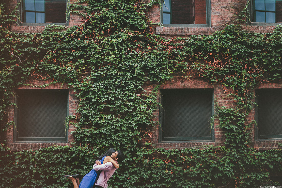 couple standing in front of a red brick wall with green ivy for their engagement photos