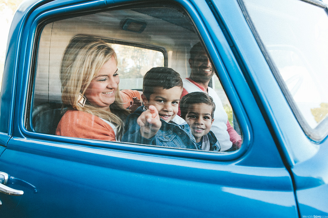 Family sitting in old pickup truck for family photos