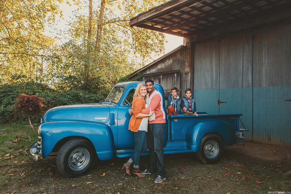 Mom and dad hugging with twin boys and an old blue pickup truck for this Fall Family Photo session
