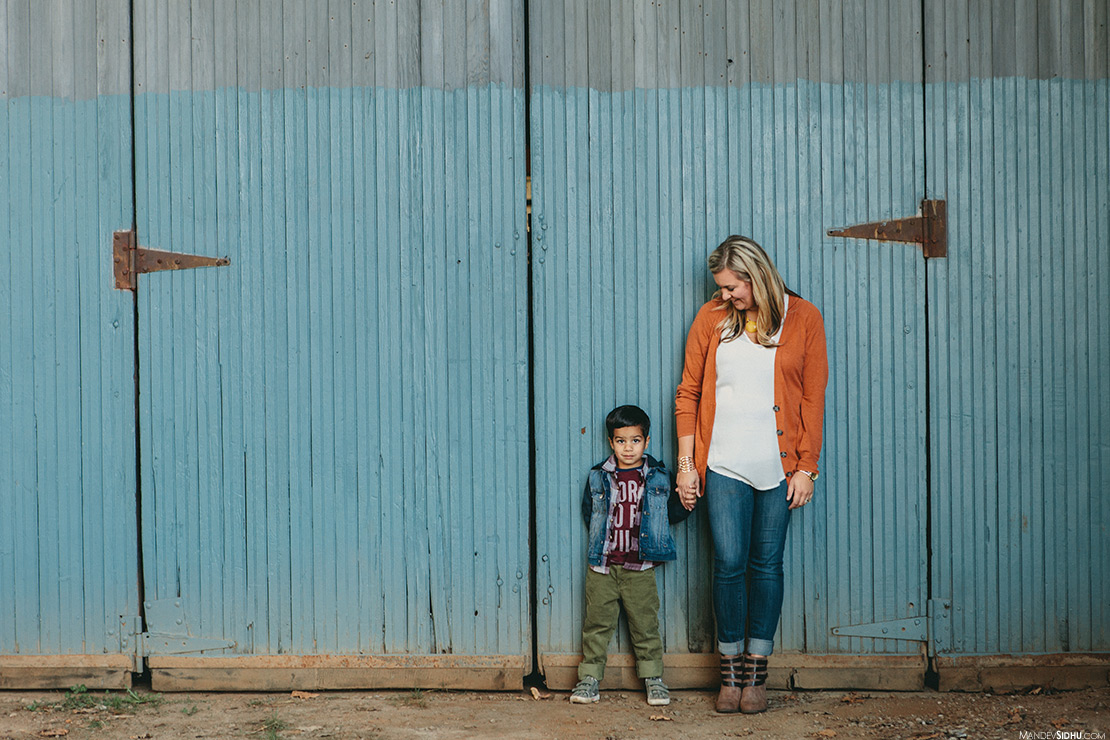 mom and son holding hand against an old barn for family photo