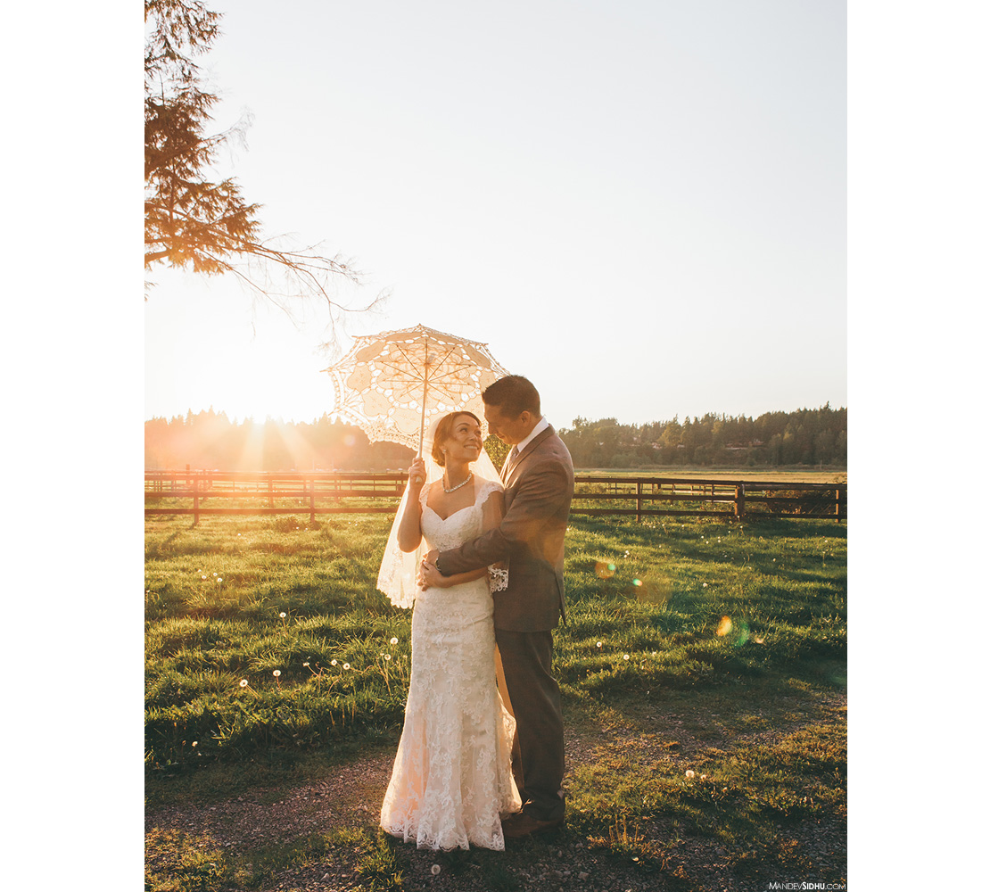 bride and groom standing in field with sunset