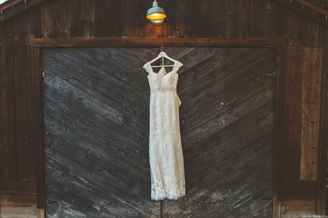 bride's white dress hanging on barn in front of wooden doors